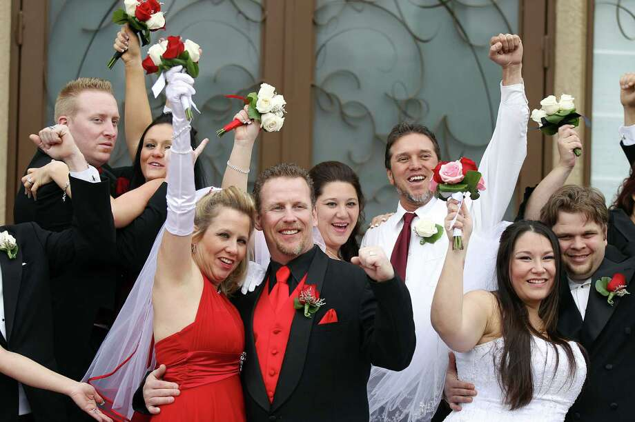 A dozen newlyweds pose for photos after participating in a mass wedding as part of a radio station contest at the Little Chapel of the Flowers on December 12, 2012 in Las Vegas, Nevada. Couples around the world are hoping that a once-in-a-lifetime event, the date 12/12/12, will bring added luck to their marriages if they tie the knot today. This will be the last such triple date for almost a century, until January 1, 2101. Photo: Isaac Brekken, Getty Images / 2012 Getty Images