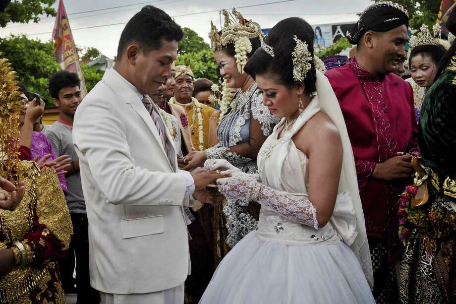 Brides and grooms exchange rings during a mass wedding ceremony on December 12, 2012 in Yogyakarta, Indonesia. Twelve couples participated in a mass wedding as today saw a surge in marriage across the globe to mark the once in a century date of 12/12/12. Photo: Ulet Ifansasti, Getty Images / 2012 Getty Images