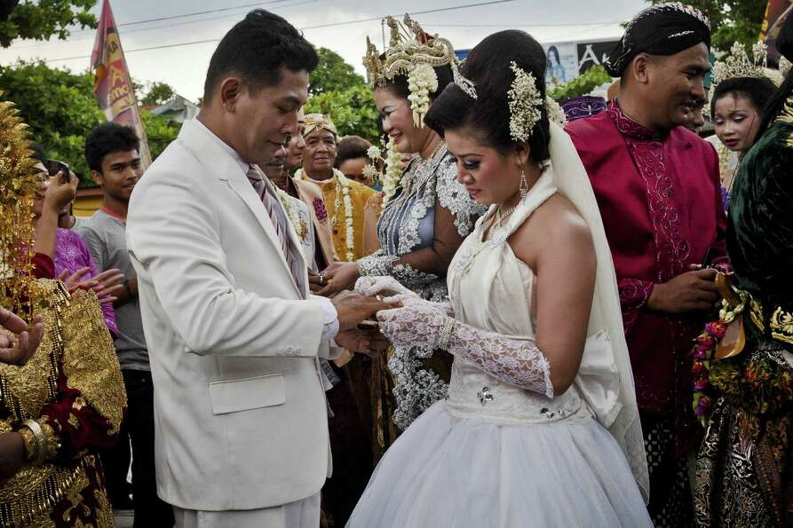 Brides and grooms exchange rings during a mass wedding ceremony on December 12, 2012 in Yogyakarta,