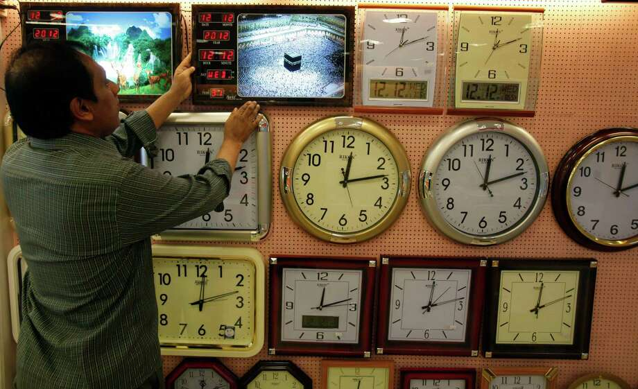 An Indian shopkeeper shows a wall clock to a customer at 12hrs 12 minutes on 12/12/12 at a shop in Hyderabad, India, Wednesday, Dec. 12, 2012. The date 12/12/12, seen as auspicious by astrologers, saw an influx of mothers to local hospitals looking to give birth on the date which won't happen again for nearly 100 years, local media reported. Photo: Mahesh Kumar A, Associated Press / AP