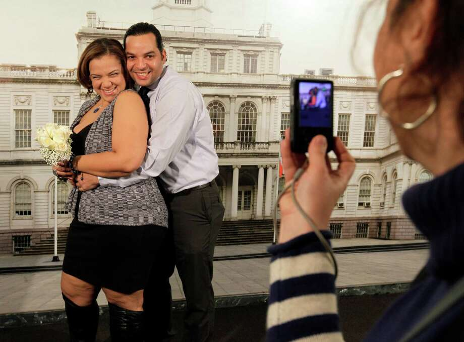 Francisco Mena, and his new wife, Carolina Mena, of the Washington Heights neighborhood of New York, pose for photos in the Office of the City Clerk, in New York,  after their wedding, Wednesday, Dec. 12, 2012. New York Mayor Michael Bloomberg turned the Manhattan Marriage Bureau into a gleaming 24,000-square-foot wedding palace in 2009, saying he was setting out to give Vegas a run for its money. Photo: Richard Drew, Associated Press / AP
