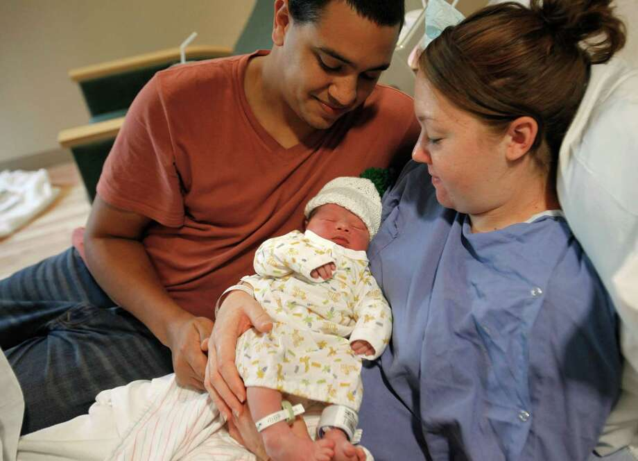Bryatt and Stephanie Finger of Bangor, Mich. pose for photos with their newborn baby Kamden, born 5:46 a.m. at Bronson Methodist Hospital on Wednesday, Dec. 12, 2012. Photo: Mark Bugnaski, Associated Press / The Kalamazoo Gazette