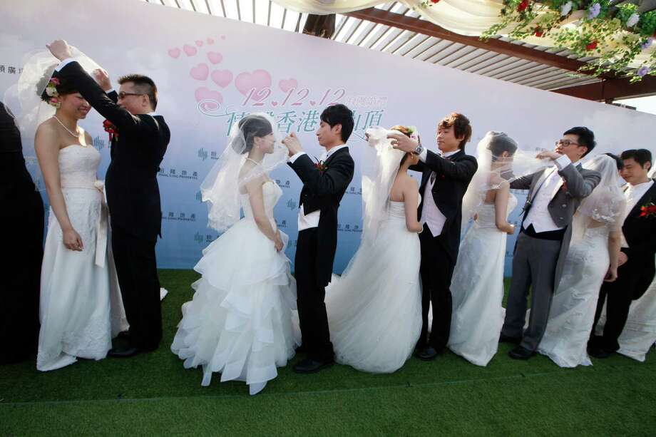 Twelve couples attend a mass wedding ceremony at the Peak in Hong Kong, Wednesday, Dec. 12, 2012. At least 700 couples are expected to get married in the date 12/12/12, the last such triple-date in this year in Hong Kong as they believe the date will bring them everlasting love. Photo: Kin Cheung, Associated Press / AP