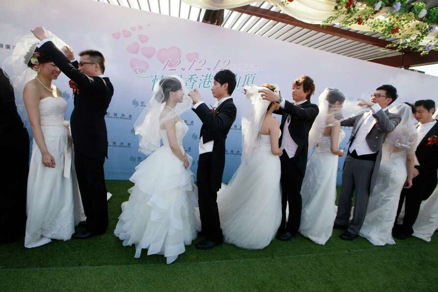 Twelve couples attend a mass wedding ceremony at the Peak in Hong Kong, Wednesday, Dec. 12, 2012. At
