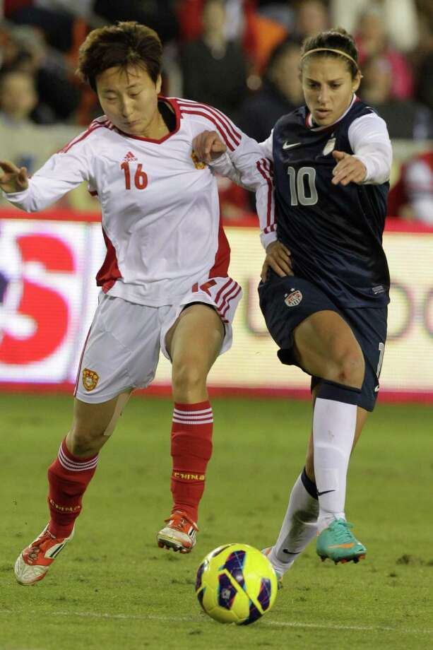China's Wang Chen, left, and USA's Carli Lloyd scramble for the ball  during the second half of woman's soccer game at BBVA Compass Stadium Sunday, Jan. 9, 2000, in Houston. Photo: Melissa Phillip, Houston Chronicle / © 2012 Houston Chronicle