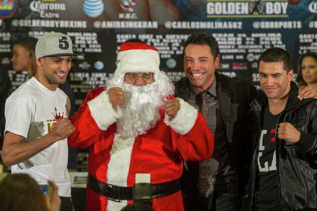 "Golden Boy Promotions president Oscar De La Hoya second from right, and someone dressed as Santa Claus present Amir ""King"" Khan, left, and Carlos Molina, right, during a boxing news conference in Los Angeles Wednesday, Dec. 12, 2012. Khan and Molina are scheduled to fight in a junior welterweight bout on Saturday at the Los Angeles Sports Arena. Photo: Damian Dovarganes, Associated Press / AP"