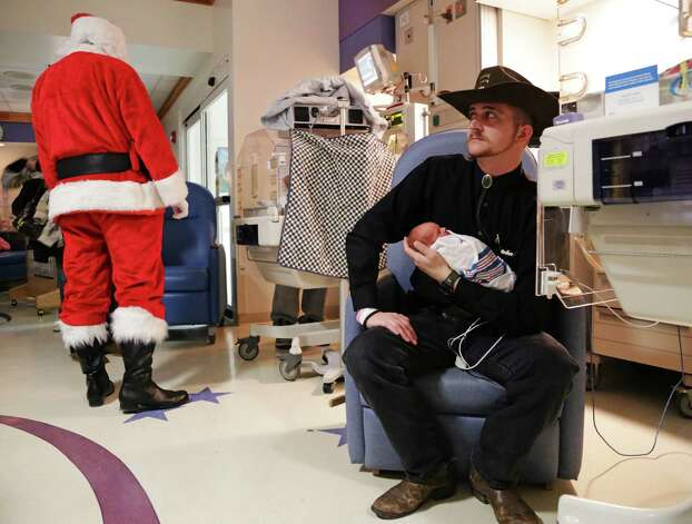 Timothy Williams, of Davison, holds his son Isaiah Creel, while waiting to have a photo taken with Santa Claus in the Neonatal Intensive Care Unit facility at Hurley Medical Center in Flint, Mich. Wednesday, Dec. 12, 2012 . Over thirty families had an opportunity to have a complimentary photo with Santa Claus along with a scrapbook page and frames as a way to make a special day for their families since they can't be together. Photo: Ryan Garza, Associated Press / The Flint Journal