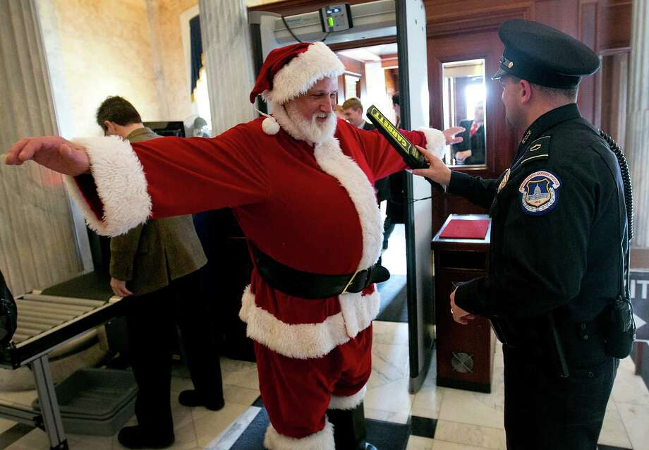 """Capitol Hill police check an unidentified man dressed as Santa Claus with a metal detector as he enters the U.S. Capitol on his way to Speaker of the House John Boehner's office on December 12, 2012 in Washington, DC. The man was working with the group Catholics United, and wanted to urge Speaker of the House John Boehner to pass pending """"fiscal cliff"""" legislation before Christmas. Photo: Win McNamee, Getty Images / 2012 Getty Images"""