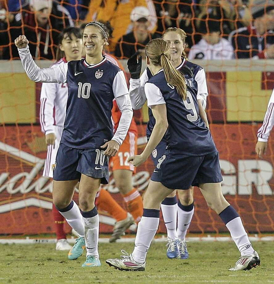 HOUSTON, TX - DECEMBER 12: Carli Lloyd #10 of the United States celebrates her score with Heather O'Reilly #9 as dejected China team looks on in the second half at BBVA Compass Stadium on December 12, 2012 in Houston, Texas. USA won 4-0. (Photo by Bob Levey/Getty Images) Photo: Bob Levey, Getty Images