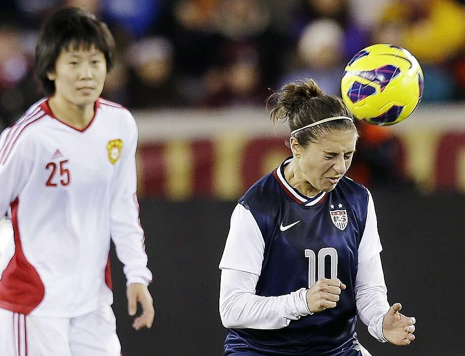 United States' Carli Lloyd (10) heads the ball in front of China's Zhang Rui during the first half of an exhibition soccer match, Wednesday, Dec. 12, 2012, in Houston. (AP Photo/David J. Phillip) Photo: David J. Phillip, Associated Press