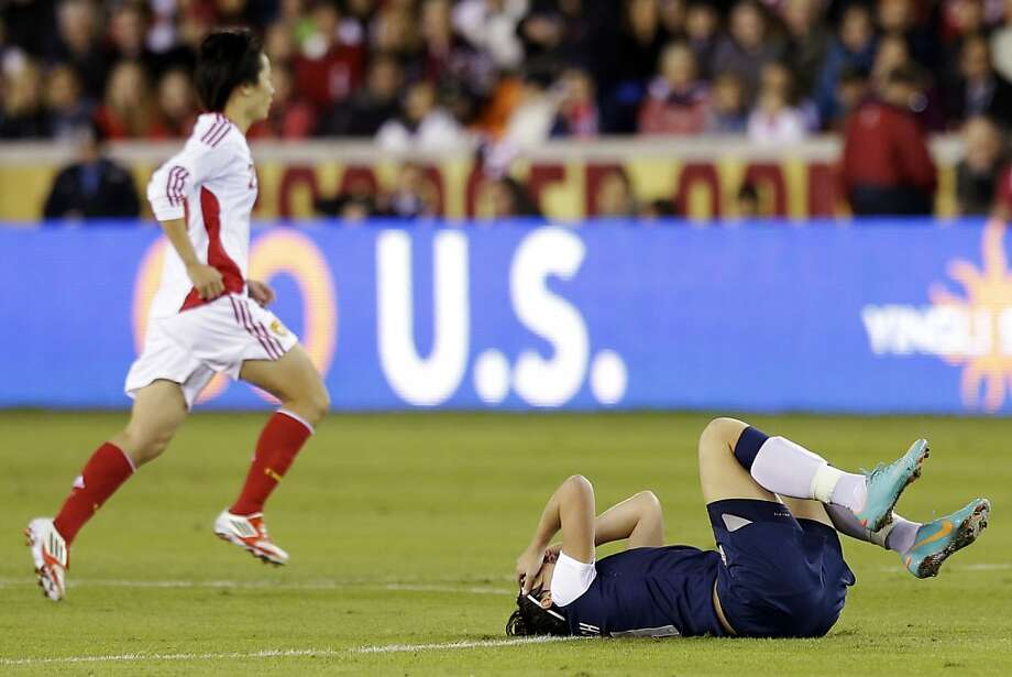 United States' Abby Wambach lays on the ground after hurting her head in front of China's Huang Yini during the first half of an exhibition soccer match, Wednesday, Dec. 12, 2012, in Houston. (AP Photo/David J. Phillip) Photo: David J. Phillip, Associated Press