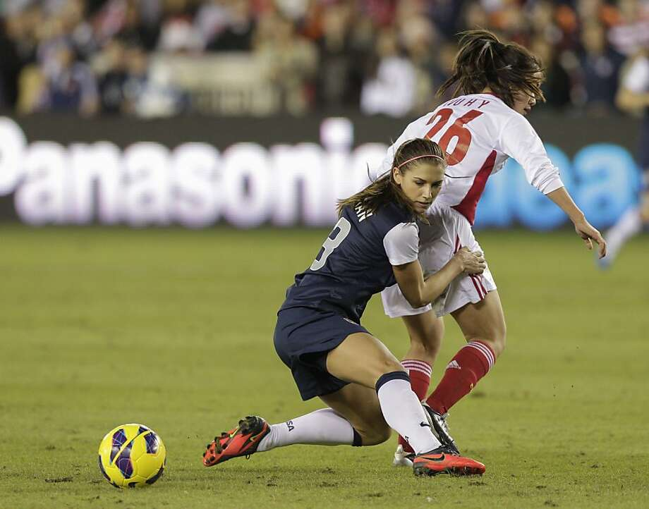 HOUSTON, TX - DECEMBER 12:  Alex Morgan #13 of the United States collides with Wu Haiyan #26 of China in the second half at BBVA Compass Stadium on December 12, 2012 in Houston, Texas. USA won 4-0. (Photo by Bob Levey/Getty Images) Photo: Bob Levey, Getty Images