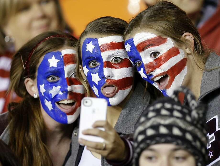 United States fans take their own picture with a mobile device before an exhibition soccer match against China, Wednesday, Dec. 12, 2012, in Houston. (AP Photo/David J. Phillip) Photo: David J. Phillip, Associated Press