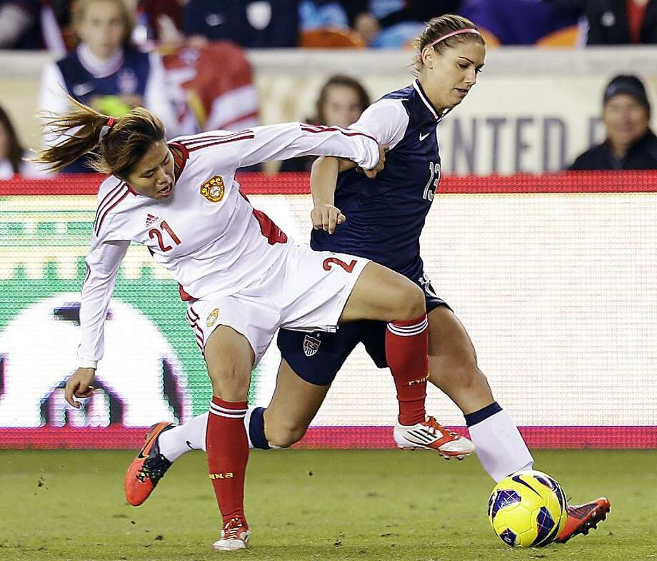China's Wang Lisi and United States' Alex Morgan (13) go after the ball during the first half of an exhibition soccer match, Wednesday, Dec. 12, 2012, in Houston. (AP Photo/David J. Phillip) Photo: David J. Phillip, Associated Press