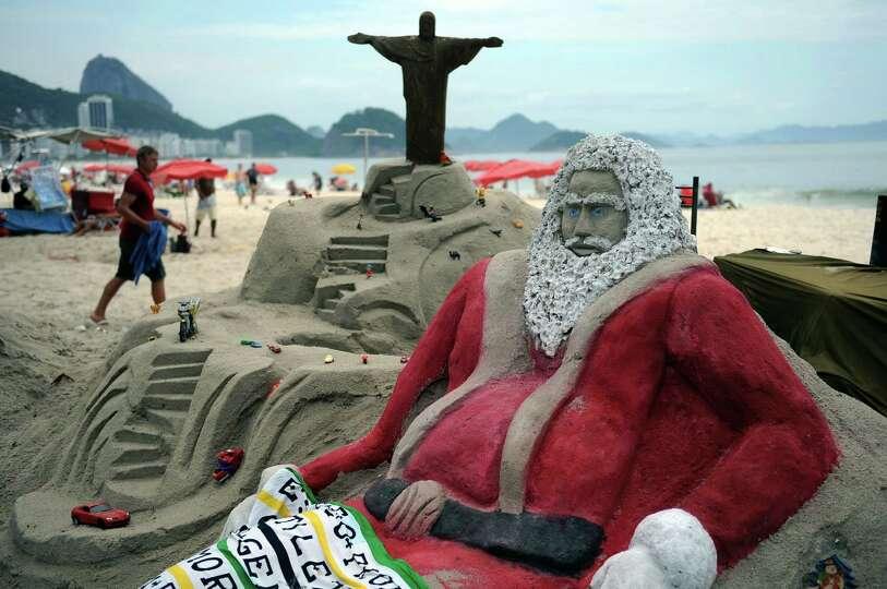 Tourists remain at Copacabana beach near a sand sculpture depicting Santa Claus in Rio de Janeirro,