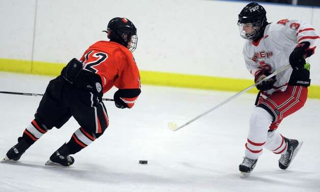 Fairfield Prep's Matt Wikman controls the puck as Ridgefield's Jamie Kelly defends during their hockey game Wednesday, Dec. 12, 2012 at Wonderland of Ice in Bridgeport, Conn. Photo: Autumn Driscoll / Connecticut Post