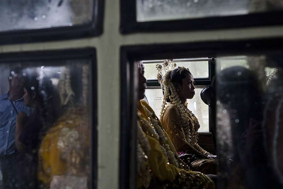 YOGYAKARTA, INDONESIA - DECEMBER 12:  A bride sit inside a bus before parade during a mass wedding ceremony on December 12, 2012 in Yogyakarta, Indonesia.  Twelve couples participated in a mass wedding as today saw a surge in marriage across the globe to mark the once in a century date of 12/12/12.  (Photo by Ulet Ifansasti/Getty Images) Photo: Ulet Ifansasti, Getty Images