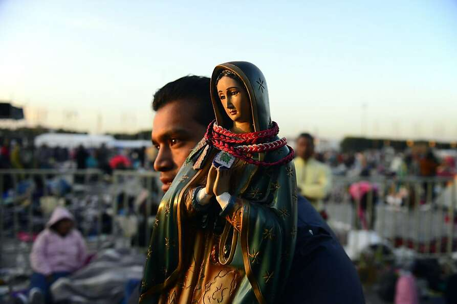 A pilgrim holds an image of the Guadalupe Virgin at the Basilica de Guadalupe in Mexico City on Dece