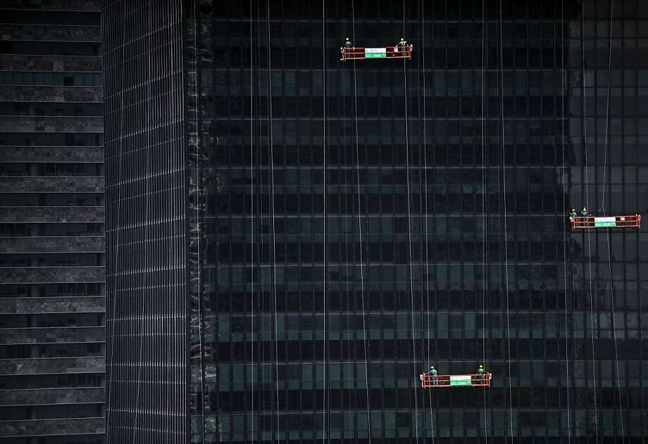 Squeegee squad: Window washers clean the facade of a 40-story building containing the headquarters of the National Bank of Economic Social Development in Rio de Janeiro. Photo: Vanderlei Almeida, AFP/Getty Images