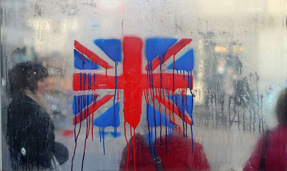A painted British union flag is seen as people wait at a bus stop on the loyalist Shankill road in Belfast, Northern Ireland on December 12, 2012. Tensions have risen in the British province since councillors voted on December 3 to limit the number of days the Union Jack can fly over the City Hall to 17, outraging loyalists who believe Northern Ireland should retain strong links to Britain. AFP PHOTO/ PETER MUHLYPETER MUHLY/AFP/Getty Images Photo: Peter Muhly, AFP/Getty Images