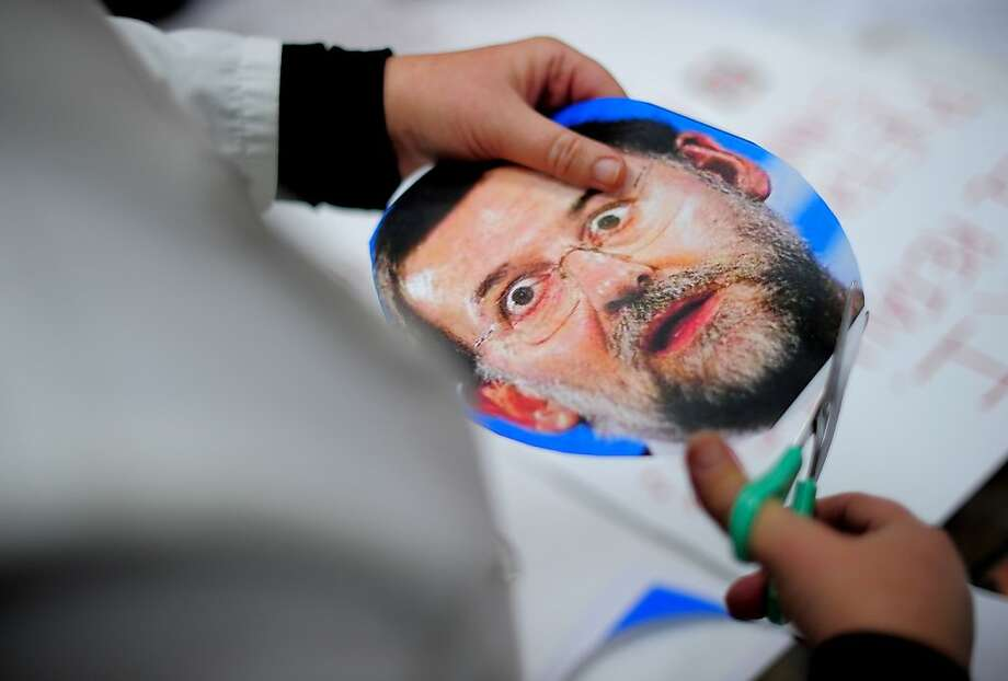 A medical worker cuts a board displaying a picture of Spain's Prime Minister Mariano Rajoy during a protest against government health austerity cuts in the Vall D'Hebron hospital in Barcelona on December 12, 2012. Nationally, Prime Minister Mariano Rajoy's government has slashed health spending by seven billion euros ($9.1 billion) a year as part of a campaign to squeeze 102 billion euros out of the crisis-racked country's budget by 2014. AFP PHOTO / JOSEP LAGOJOSEP LAGO/AFP/Getty Images Photo: Josep Lago, AFP/Getty Images