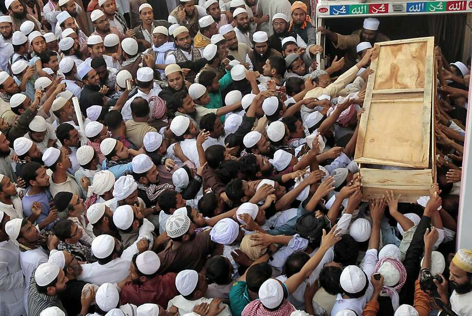 Supporters try to touch the coffin containing the body of Islami Oikya Jote party leader Mufti Fazlul Huq Amini in Dhaka, Bangladesh, Wednesday, Dec. 12, 2012. Islamic politician Amini died at a city hospital early Wednesday. He was 69. (AP Photo/A.M. Ahad) Photo: A.M.Ahad, Associated Press