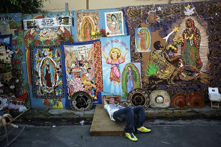 A street vendor lays next to religious merchandise portraying the Virgin of Guadalupe near the Basilica de Guadalupe in San Salvador on December 12, 2012. Salvadorean faithfuls celebrated the appearance of the Virgin of Guadalupe to Juan Diego in 1531. AFP PHOTO/ Jose CABEZASJose CABEZAS/AFP/Getty Images Photo: Jose Cabezas, AFP/Getty Images