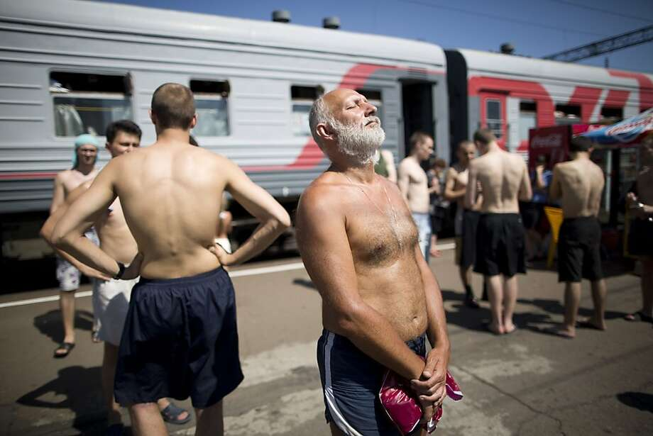 "FILE PHOTO: ""BEST PHOTOS OF 2012"" (***BESTOF2012***): Passengers from the Novorossiysk-Moscow train, operated by OAO Russian Railways, sunbathe on a platform at Liski station in Voronezh region,  Russia, on Sunday, July 15, 2012. Russia's government plans to sell stakes in its rail monopoly, grain trader, biggest shipper, nanotechnology holding and largest banks within 18 months as it loosens its grip on an economy dominated by commodity exports. Photographer: Andrey Rudakov/Bloomberg Photo: Andrey Rudakov, Bloomberg"