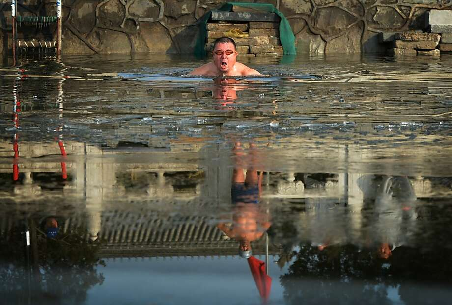 This photo taken on December 11, 2012 shows a Chinese man swimming in icy waters in minus 3 Centigrade temperatures (28 F) at the frozen Houhai Lake of Beijing.  Winter swimming is especially popular amongst the elderly and retired as it is believed to improve circulation and benefit health, and also said to increase the level of mental awareness, release stress, remove aches and pains, increase vitality and keep skin looking younger - and of course, an overall feeling of well-being.      AFP PHOTO/Mark RALSTONMARK RALSTON/AFP/Getty Images Photo: Mark Ralston, AFP/Getty Images