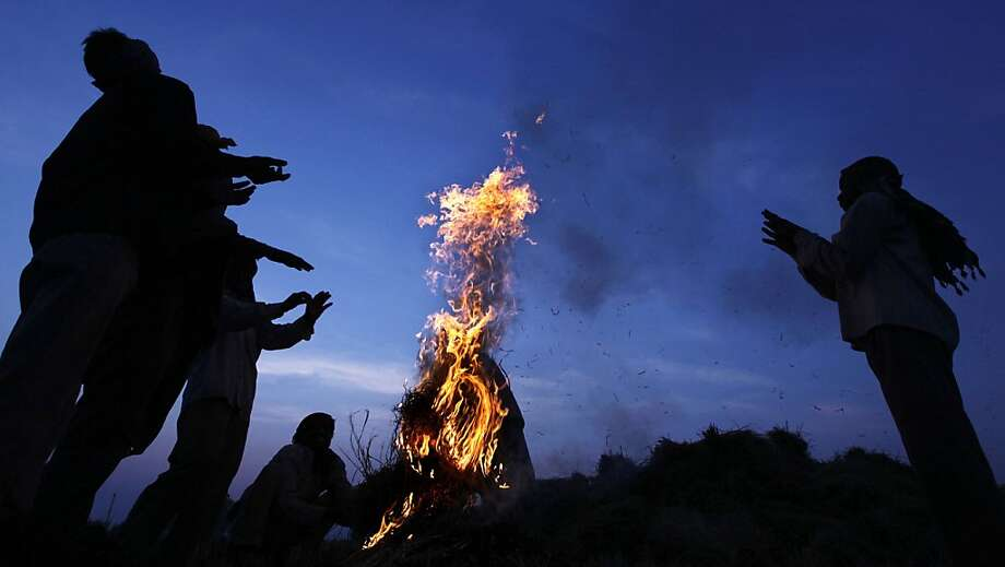 Indian labourers warm themselves around a bonfire in a rice paddy field during a cold morning on the outskirts of Jammu in the state of Jammu and Kashmir on December 12, 2012.  The global rice trade is expected to decline by one million tonnes to 34.2 million tonnes in 2012, largely as a result of reduced import demand from Asian countries, the UN's Food and Agriculture Organisation (FAO) said. AFP PHOTO/ STRSTRDEL/AFP/Getty Images Photo: Strdel, AFP/Getty Images