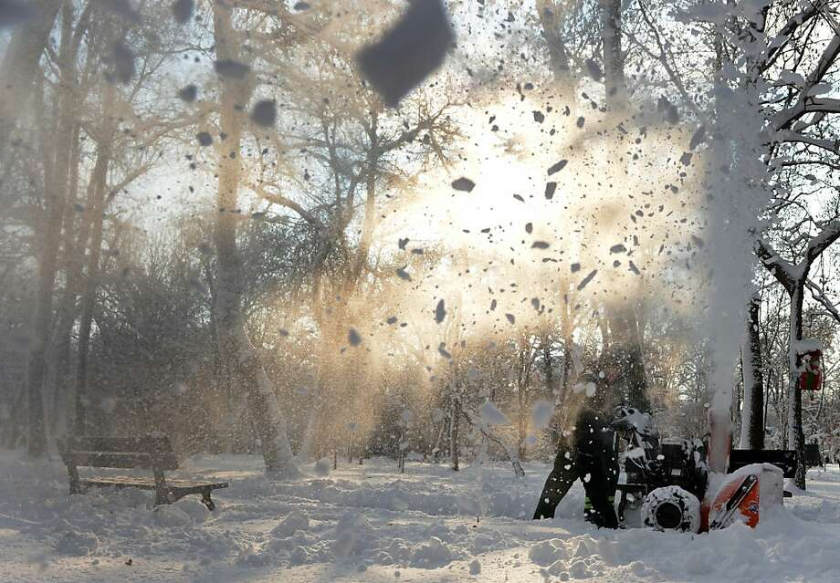 A worker removes snow by using a snow blower in a park in Bucharest, on December 12, 2012. The southern half of the country and the Moldova region were hit by heavy snowfalls and blizzards. Temperatures in the Romanian capital Bucharest were predicted to fall down to minus 20 degrees Celsius at night. AFP PHOTO / DANIEL MIHAILESCUDANIEL MIHAILESCU/AFP/Getty Images Photo: Daniel Mihailescu, AFP/Getty Images