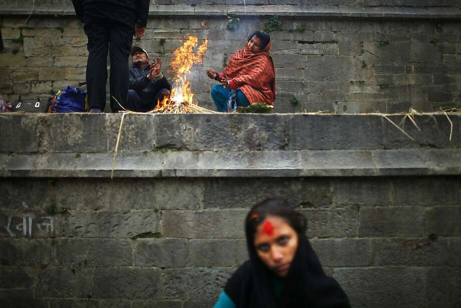 Nepalese devotees warm themselves on a fire during the Bala Chaturdasi festival at the Pashupatinath Temple in Katmandu, Nepal, Wednesday, Dec. 12, 2012. Bala Chaturdashi is celebrated in memory of departed family members by lighting oil lamps and scattering seven types of grains along a prescribed route. (AP Photo/Niranjan Shrestha) Photo: Niranjan Shrestha, Associated Press