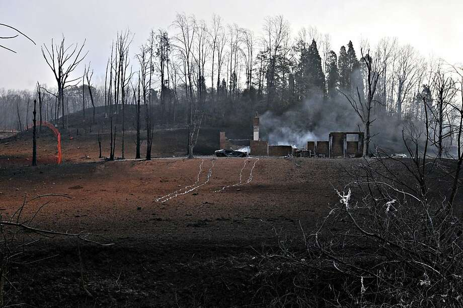 Charred trees and homes are left along Interstate 77 Wednesday Dec. 12, 2012, where a gas line ruptured and exploded in Sissonville, W.Va. Tuesday. The interstate pavement melted from the heat of the explosion, shutting down Interstate 77 overnight. But the northbound lanes of the interstate reopened at 8am Wednesday, and the southbound lanes a few hours later. Investigations into what caused the massive blast in a 20-inch Columbia Gas Transmission line are under way.  (AP Photo/Charleston Daily Mail,Tom Hindman) Photo: Tom Hindman, Associated Press