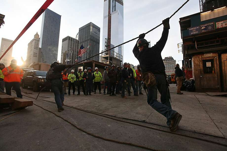 NEW YORK, NY - DECEMBER 12:  Workers pull a rope as they prepare the first piece of the spire to be hoisted atop One World Trade Center on December 12, 2012 in New York City.  The first of 18 sections of spire was hoisted atop the 104-story building by crane this morning.  (Photo by Mario Tama/Getty Images) Photo: Mario Tama, Getty Images