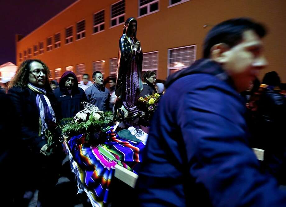 Worshipers carry a small statue of the Virgin of Guadalupe during a procession celebrating the virgin's feast day, Wednesday, Dec. 12, 2012, in Passaic, N.J. Catholic Mexicans living in New Jersey pay homage to the virgin on Dec. 12, to observe what they believe was an apparition of the virgin on Juan Diego, an indigenous man, on the hill of Tepeyac in Mexico City on Dec. 12, 1531. (AP Photo/Julio Cortez) Photo: Julio Cortez, Associated Press