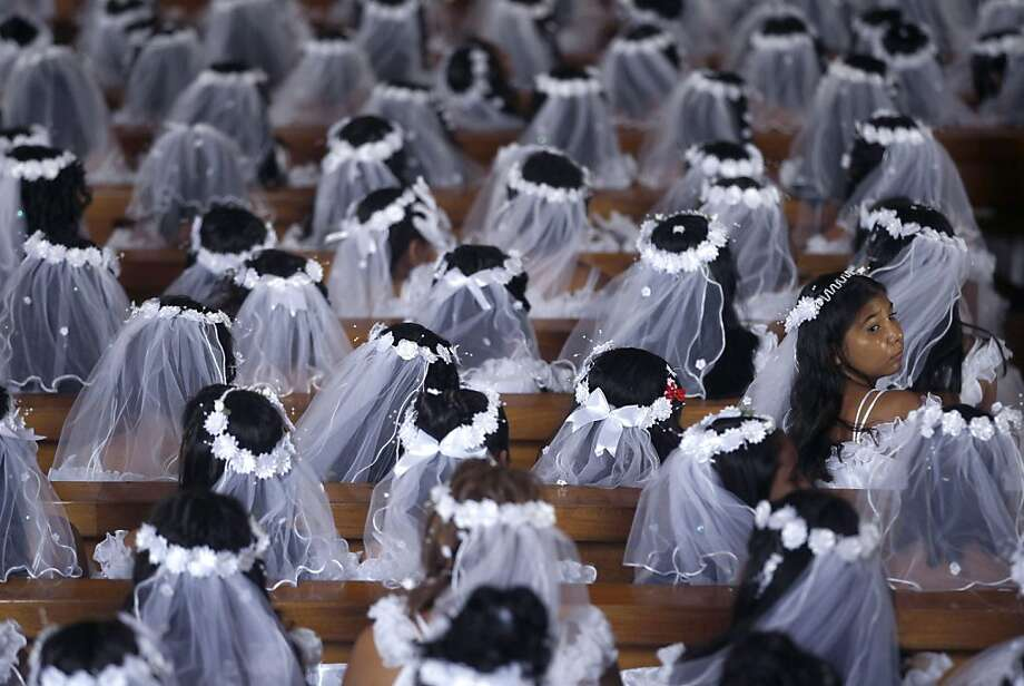 Girls donning their first communion veils sit in the pews of the Metropolitan Cathedral, during a First Holy Communion service, in Managua, Nicaragua, Dec. 12, 2012. Around 550 children, aged between 8-16, marked the Virgin of Guadalupe's feast day by receiving for the first time the Sacrament of the Holy Eucharist, which is the eating of consecrated bread and drinking of consecrated wine. The government sponsored the religious event, buying the children's clothes and accessories. (AP Photo/Esteban Felix) Photo: Esteban Felix, Associated Press