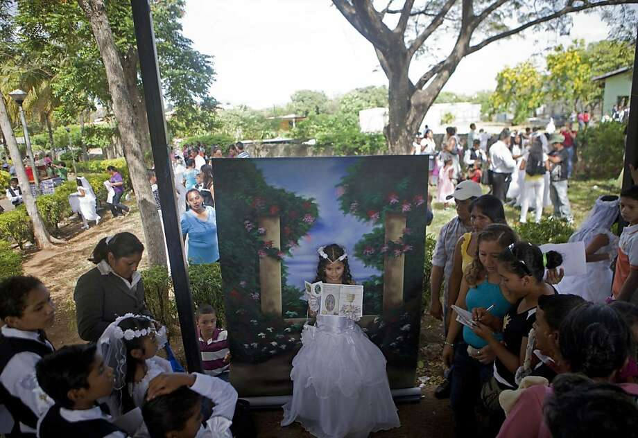 A girl poses for a portrait in her communion gown on the grounds of the Metropolitan Cathedral, in Managua, Nicaragua, Dec. 12, 2012. Around 550 children, aged between 8-16, marked the Virgin of Guadalupe's feast day by making their Holy First Communion, receiving for the first time the Sacrament of the Holy Eucharist, which is the eating of consecrated bread and drinking of consecrated wine inside the cathedral. The government sponsored the religious event, buying the children's clothes and accessories. (AP Photo/Esteban Felix) Photo: Esteban Felix, Associated Press