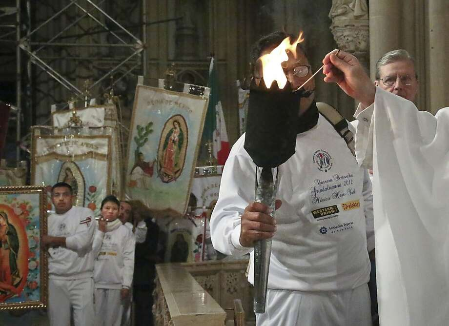 "A torch carried from Mexico City to New York as part of a relay called ""Carrera Antorcha Guadalupana 2012"" is re-lighted during a Mass at St. Patrick's Cathedral marking the end of the relay in New York, Wednesday, Dec. 12, 2012.  The relay starts at Mexico's Basilica of Guadalupe and ends at New York's St. Patrick's Cathedral, passing through every state where families of migrants reside and symbolizes ""two nations and thousands of families divided by the border,"" according to the event website.  Every Dec. 12, Catholics celebrate the feast day of the Virgin of Guadalupe, Mexico's patron saint. (AP Photo/Bebeto Matthews) Photo: Bebeto Matthews, Associated Press"