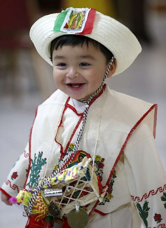 Joseph Villanueva, 18-months, is dressed in Mexican indigenous clothing during a celebration of  Virgin of Guadalupe's feast day at Our Lady of Fatima Church, Wednesday, Dec. 12, 2012, in Passaic, N.J. Catholic Mexicans living in New Jersey pay homage to the Virgin on Dec. 12, to observe what they believe was an apparition of the Virgin seen by Juan Diego, an indigenous man, on the hill of Tepeyac in Mexico City on Dec. 12, 1531. (AP Photo/Julio Cortez) Photo: Julio Cortez, Associated Press