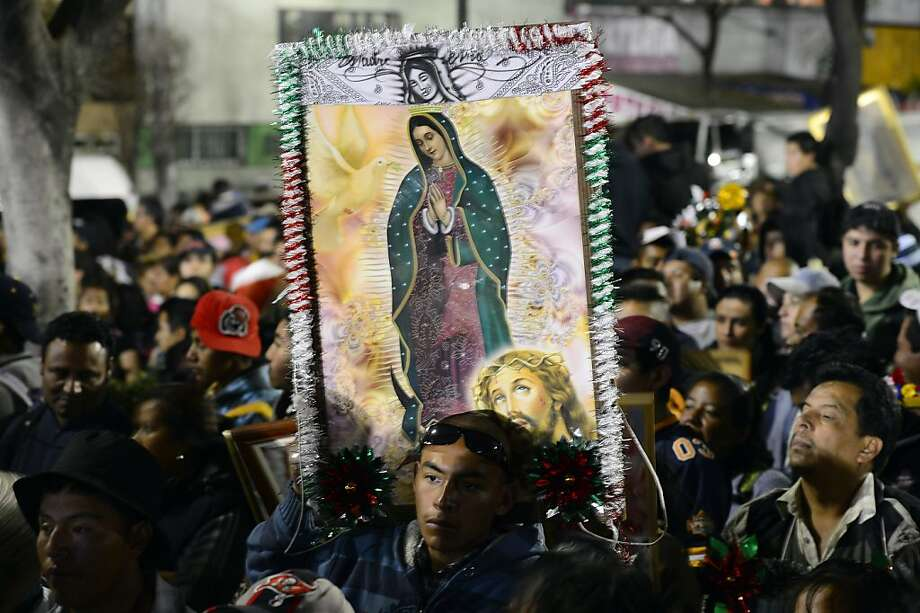 Pilgrims hold an image of Guadalupe Virgin before the birthday of the Guadalupe Virgin at the Basilica de Guadalupe in Mexico City on December 11, 2012. Mexicans celebrated the appearance of the Virgin of Guadalupe to Juan Diego in 1531.    AFP PHOTO/Alfredo EstrellaALFREDO ESTRELLA/AFP/Getty Images Photo: Alfredo Estrella, AFP/Getty Images