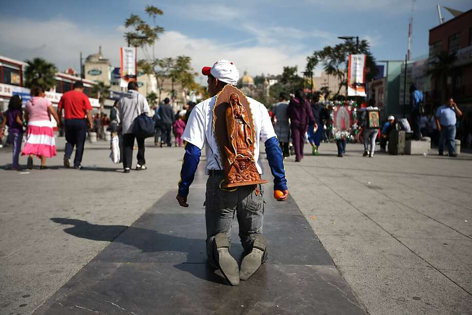 A pilgrim walks on his knees carrying an image of the Virgin of Guadalupe on his back as he makes his way to the Basilica of Guadalupe in Mexico City, Tuesday Dec. 11, 2012. Nationwide, devotees of the Virgin of Guadalupe make a pilgrimage to the basilica in honor of her Dec. 12 feast day. (AP Photo/Denisse Pohls) Photo: Denisse Pohls, Associated Press
