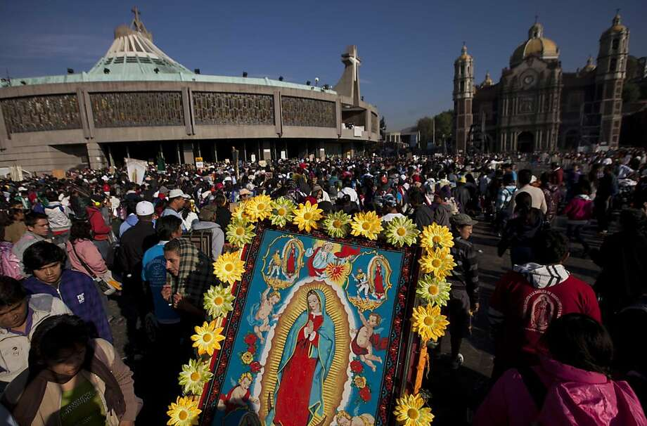 A pilgrim carries an image, framed with artificial flowers, of the Virgin of Guadalupe towards the Basilica of Guadalupe, in Mexico City, Wednesday, Dec. 12, 2012. Hundreds of thousands of people from all over the country converge on Mexico's holy Roman Catholic site, many bringing with them images or statues of Mexico's patron saint to be blessed, marking the Virgin's Dec. 12 feast day. (AP Photo/Eduardo Verdugo) Photo: Eduardo Verdugo, Associated Press