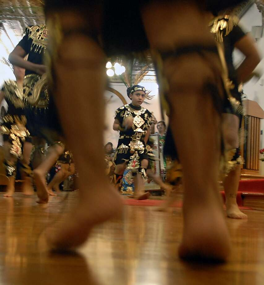 Local dancers dressed in traditional clothing take their turns dancing as they entered the Virgin of Guadalupe church in Brownsville, Texas, during a celebration of Virgin of Guadalupe's feast day, Wednesday, Dec. 12, 2012. (AP Photo/The Brownsville Herald, Brad Doherty) Photo: Brad Doherty, Associated Press