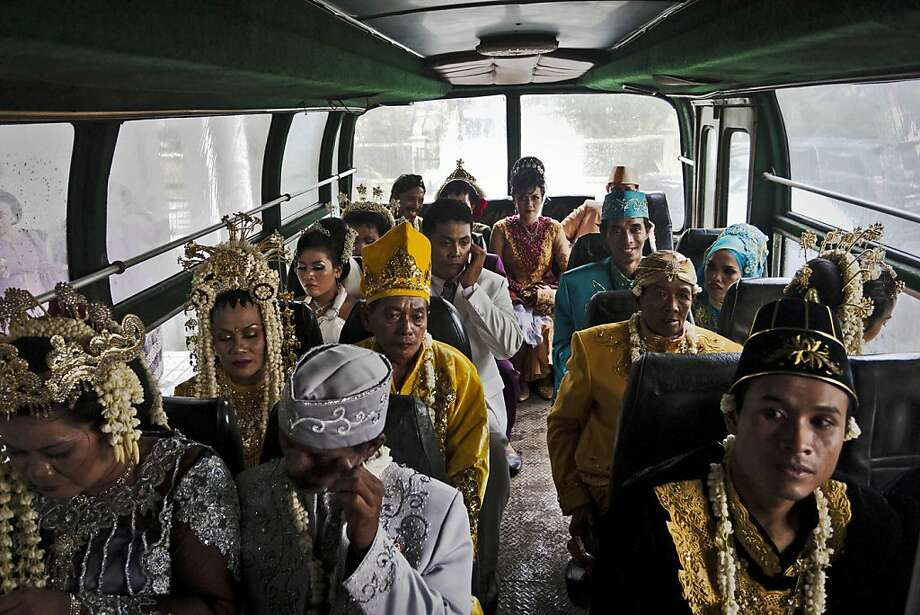 YOGYAKARTA, INDONESIA - DECEMBER 12:  Brides and grooms sit on a bus before they get ready to take part in a mass Wedding ceremony on December 12, 2012 in Yogyakarta, Indonesia. Twelve couples participated in a mass wedding as today saw a surge in marriage across the globe to mark the once in a century date of 12/12/12.  (Photo by Ulet Ifansasti/Getty Images) Photo: Ulet Ifansasti, Getty Images