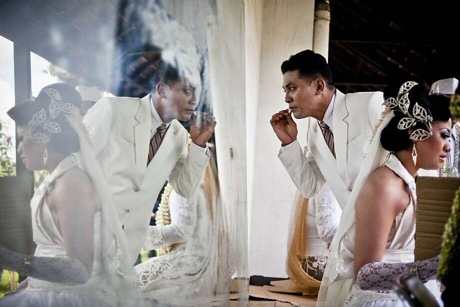 YOGYAKARTA, INDONESIA - DECEMBER 12:  A groom prepares for his own wedding as he gets ready to take part in a mass Wedding ceremony on December 12, 2012 in Yogyakarta, Indonesia. Twelve couples participated in a mass wedding as today saw a surge in marriage across the globe to mark the once in a century date of 12/12/12.  (Photo by Ulet Ifansasti/Getty Images) Photo: Ulet Ifansasti, Getty Images