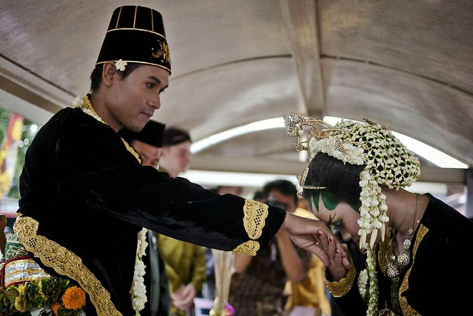 YOGYAKARTA, INDONESIA - DECEMBER 12:  Meisaroh, kiss her husband hand Moh Nasrodin, after getting married inside a lorry train during a mass wedding ceremony on December 12, 2012 in Yogyakarta, Indonesia.  Twelve couples participated in a mass wedding as today saw a surge in marriage across the globe to mark the once in a century date of 12/12/12.  (Photo by Ulet Ifansasti/Getty Images) Photo: Ulet Ifansasti, Getty Images