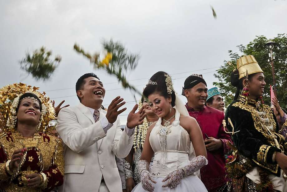 YOGYAKARTA, INDONESIA - DECEMBER 12:  Bride and groom couples celebrate their marriage during a mass wedding ceremony on December 12, 2012 in Yogyakarta, Indonesia. Twelve couples participated in a mass wedding as today saw a surge in marriage across the globe to mark the once in a century date of 12/12/12.  (Photo by Ulet Ifansasti/Getty Images) Photo: Ulet Ifansasti, Getty Images