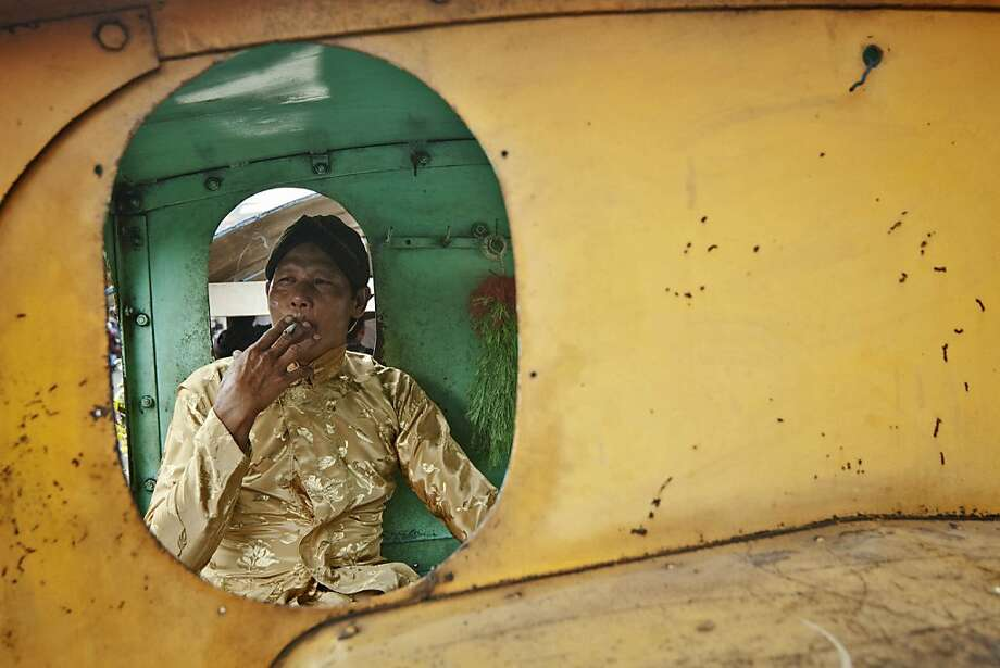 YOGYAKARTA, INDONESIA - DECEMBER 12:  A man smokes in a lorry locomotive during a mass wedding ceremony on December 12, 2012 in Yogyakarta, Indonesia. Twelve couples participated in a mass wedding as today saw a surge in marriage across the globe to mark the once in a century date of 12/12/12.  (Photo by Ulet Ifansasti/Getty Images)  *** BESTPIX *** Photo: Ulet Ifansasti, Getty Images