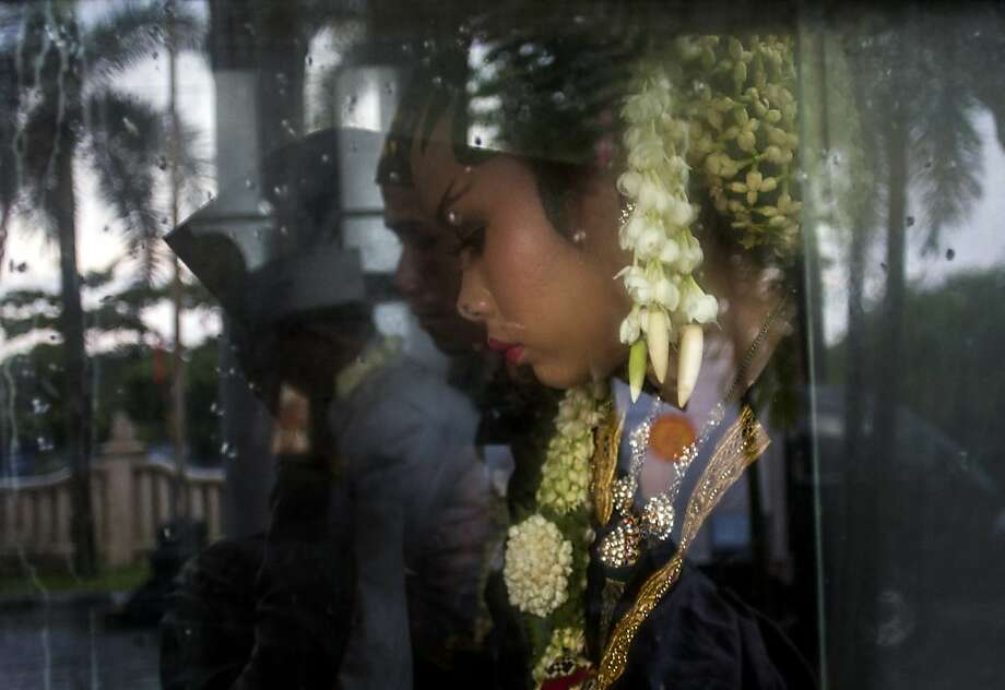 Meisaroh, a bride, sits inside a bus during a mass wedding organized for the poor in Yogyakarta, Indonesia, Wednesday, Dec. 12, 2012. Twelve lower-income couples participated in the event that was held at exactly at 12 o'clock on 12/12/12, a date seen as auspicious by many astrologers, which will not occur again for almost 100 years. (AP Photo/Gembong Nusantara) Photo: Gembong Nusantara, Associated Press