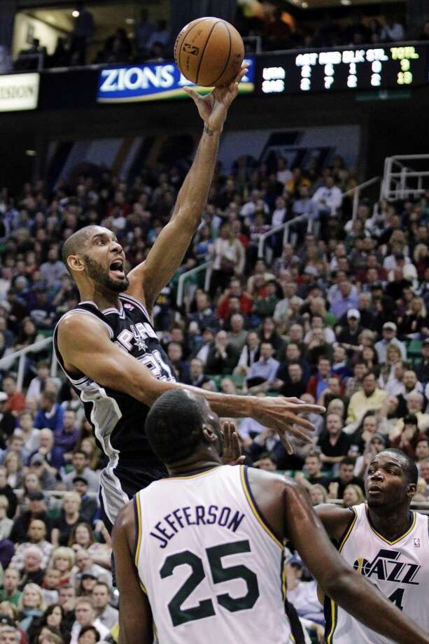 San Antonio Spurs forward Tim Duncan (21) lays the ball up against Utah Jazz center Al Jefferson (25) and forward Paul Millsap (24) in the first quarter during an NBA basketball game, Wednesday, Dec. 12, 2012, in Salt Lake City.  (Rick Bowmer / Associated Press)